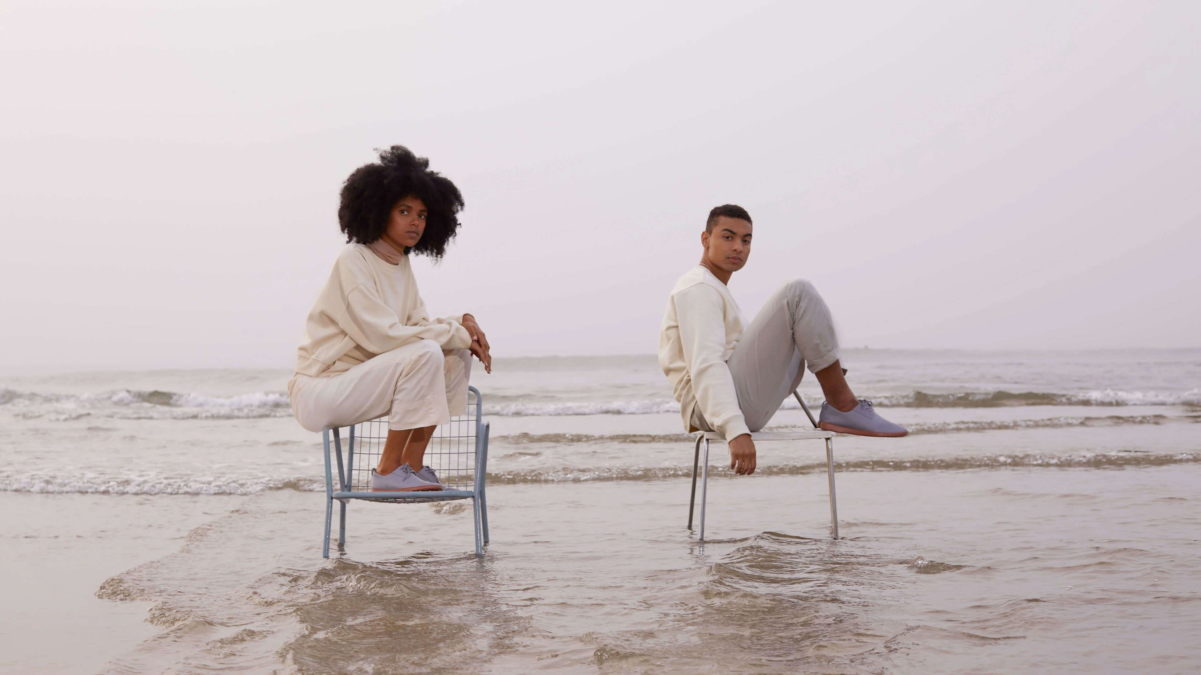Two people sitting in chairs on the beach